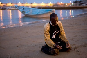 July 1, 2008: A man offer prayers of thanks after arriving at a beach on Spain's Canary island of Gran Canaria(Borja Suarez/Reuters)
