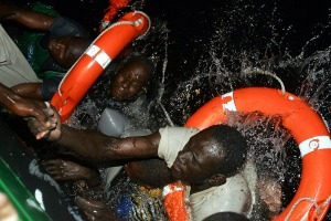 November 12, 2004: Migrants try to climb aboard a Spanish civil guard vessel after their makeshift boat capsized during a rescue operation at sea off the coast of Fuerteventura. Of the 36 in the boat, 29 were rescued (Juan Medina/ Reuters)